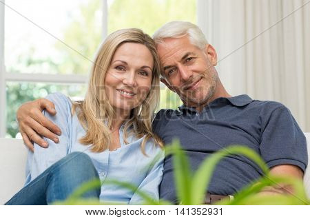 Romantic senior couple sitting on a sofa and looking at camera. Portrait of a mature couple enjoying