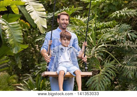 Happy son having fun on a swing with his father. Cheerful father helping son swing. Smiling dad pushing his child on the swing.