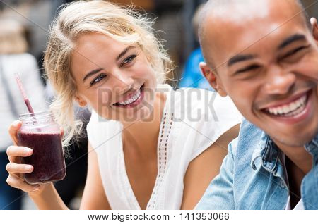 Close up of young woman drinking healthy smoothie with friend in coffee shop. Laughing friends in a cafe sitting at table together drinking healthy shake. Closeup face of smiling girl with milk shake.