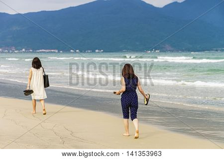 Young Girls Passing By On China Beach In Danang