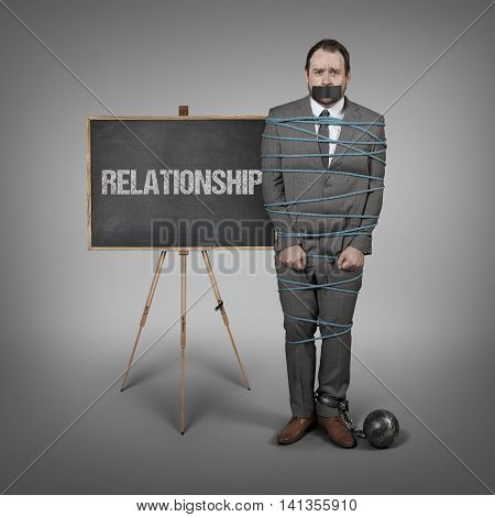 Businessman tied with rope - office setting with blackboard
