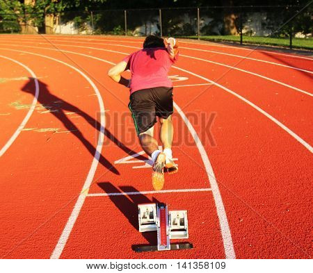 A sprinter is one step out of the blocks in lane for on a red track in lane 4