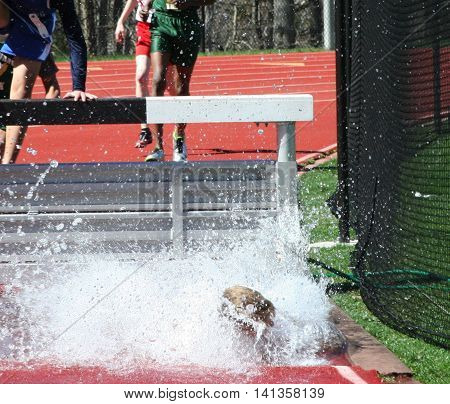 a young man is engulfed in the water during a steeplechase race in track and field