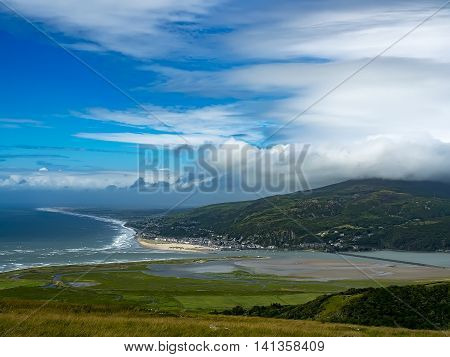 The seaside town of Barmouth or Abermaw from the hillside at Morva showing a panoramic view of the Mawddach estuary and beach with rough seas, sunshine and high stormy clouds. Wales, UK.