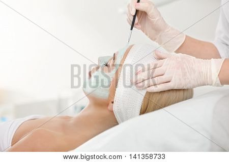 Cosmetologist applying facial mask in beauty salon