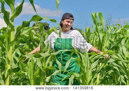 woman in the garden is happy harvest corn