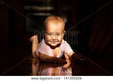 Very cute child crawling on the floor in the morning sun