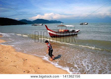 Batu Ferringhi Malaysia - January 13 2007: Little Malay boy walking in the Indian Ocean's gentle surf along the north coast of Penang Island