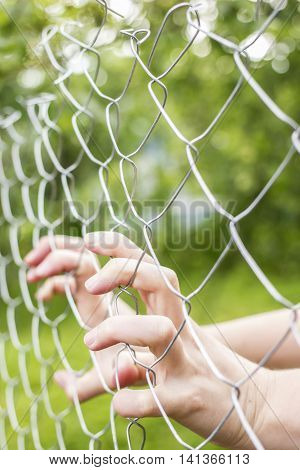 Hands holding fence outdoors in the daytime in a village