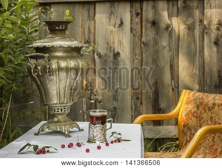 vintage copper samovar in a cup holder and a glass of hot tea stands on the table are scattered cherries and raspberries as well is worth chair in Russian village outdoors