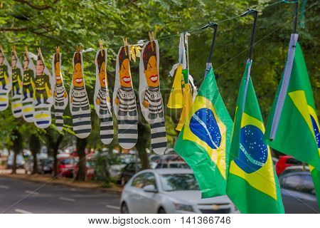 PORTO ALEGRE, BRAZIL - MAY 06, 2016: cartoon of the ex president of brazil dilma rousseff in jail suit next to brazilian flags.