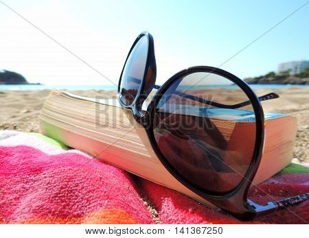 Reading at the beach. Sunglasses and book, selective focus.