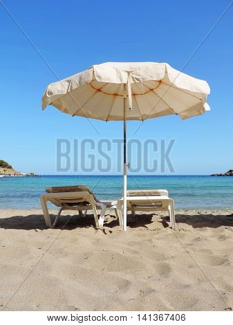 White sunshade and lounge chairs at the beach