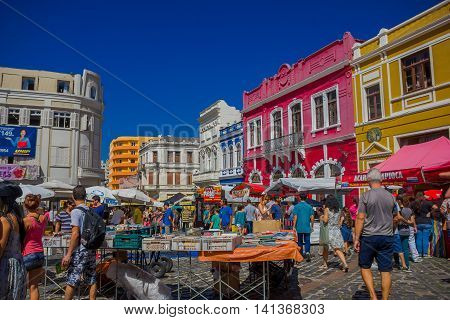CURITIBA , BRAZIL - MAY 12, 2016: people walking arround and visiting some stands at the market place, nice colorfull houses as background.