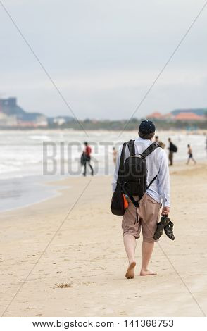 Young man passing by at the China Beach of Danang in Vietnam. No face