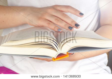 Young girl reading an open book old book. Knowledge Science. Back to school. Copy space. Toned image.