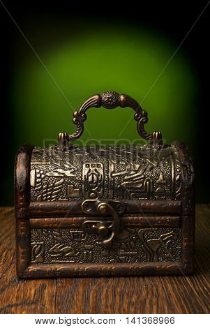 Very old chest in grunge interior  on a wooden background