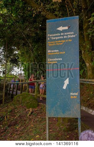 IGUAZU, BRAZIL - MAY 14, 2016: unidentified people walking through a path behind an iguazu sign showing the directions of the waterfalls and the hotel.