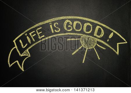 Life is good with Ribbon Banner written with yellow chalk on a blackboard