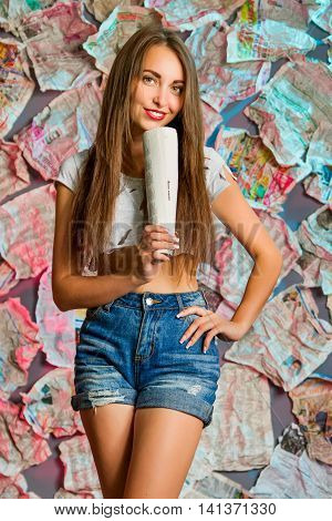 a beautiful girl with long brown hair  in denim shorts is holding a newspaper standing in the unusual background of newspapers