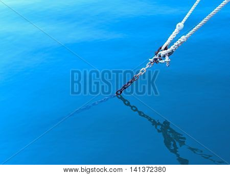 Anchored boat, rope in thew water with copy space