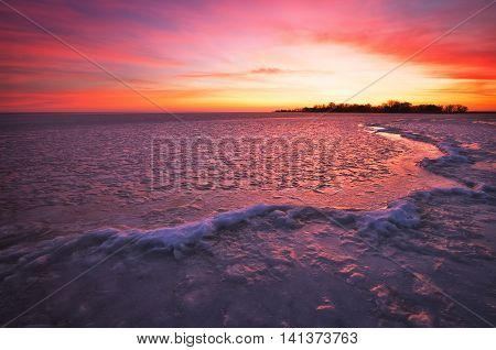 Winter landscape with sunset fiery sky and frozen river. Composition of nature.