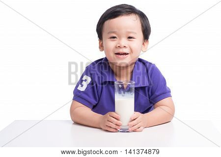 Closeup portrait of happy young boy holding glass of milk. Cute boy with milk mustache isolated on white