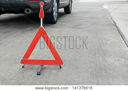 Broken car sign on a road with a broken down car