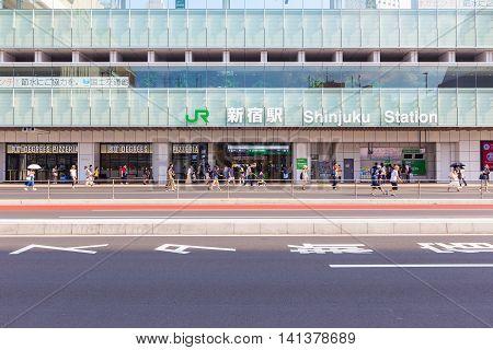TOKYO JAPAN - 17 JULY 2016 - Pedestrians walk about along empty street infront of Shinjuku Station Tokyo Japan on July 17 2016.