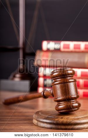 Wooden gavel with golden scales of justice  and books  on background