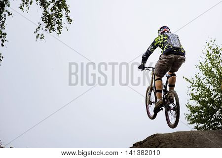 male athlete extreme jump on a bike during competition downhill