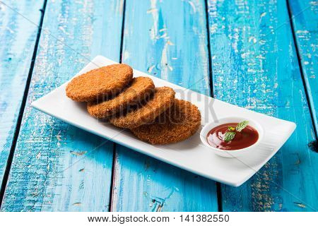 Indian chat item aloo or aalu tikki or tikiya or fried potato cake also known as ragda patties served with tomato ketchup, selective focus