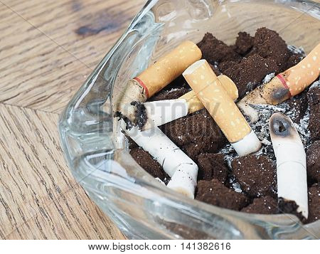 cigarette with an ashtray on the wood table