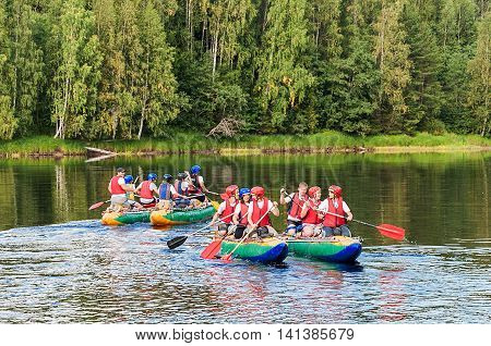 SHUYA RIVER, RUSSIA - AUGUST 25, 2015: Group of tourists sailing on two catamarans on Shuya river in Karelia