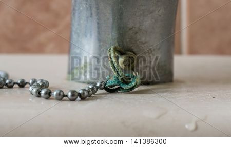 Calcium deposits on balls chain bathroom sink stopper on detail