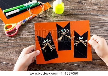 The Child Create A Greeting Card Halloween Black Cat Out Of Paper. Glue, Scissors, Leaves Velvet Pap