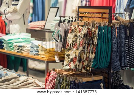 Clothing Store Interior With Summer Clothes And Flip-Flops On Foreground And Folded T-shirts On The Background