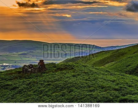 Scenic sunset of a ruined bothy by the side of an old coaching road looking down the valley of Nant Braich-y-rhiw towards the sea at Cardigan Bay, Tywyn, Wales, UK.