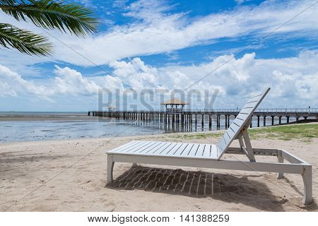 Bed white beach with a bridge extending into the sea behind.