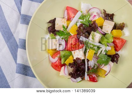 Appetising fresh Greek salad with feta cheese fresh vegetables and black olives.