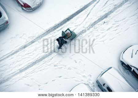 elevated view of people walking snow covered ground and parked cars