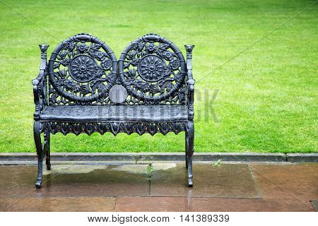 Decorative wrought iron bench in park. Space for your text.