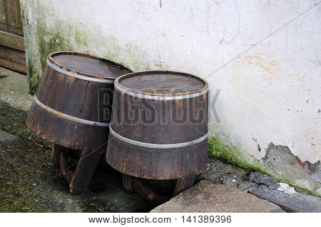 Two wooden pails leaning against a weathered wall in wuzhen town located in Zhejiang province China.