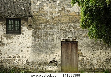 A wooden doorway leading into a weathered stone building within Wuzhen Town in Zhejiang province China.