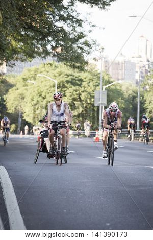 NEW YORK JUL 24 2016: David and Blake Ferrell, a father and son team, compete in the NYC Triathlon Race, biking 40 kilometers mainly on the Henry Hudson Parkway in New York.