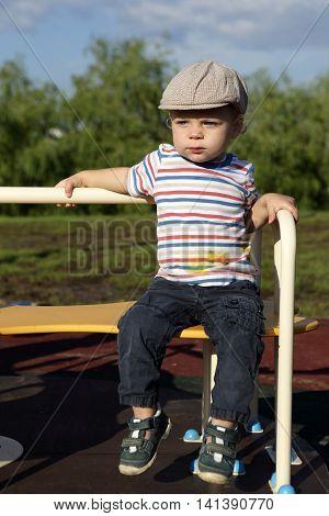 Boy Sitting On Roundabout