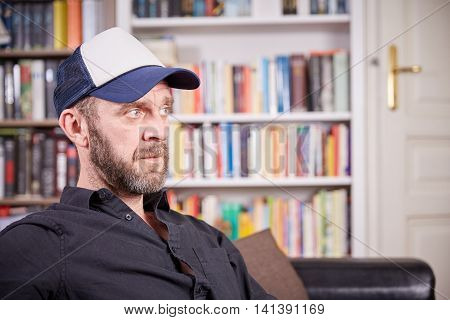 Man With Beard And Baseball Cap Sitting In A Library