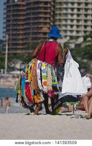 RIO DE JANEIRO, BRAZIL - AUGUST 21, 2012: Brazilian street vendor sells beach wraps on August 21, 2012 at Copacabana Beach, Rio de Janeiro. Brazil.