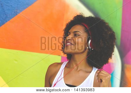 Young black woman dancing while listening to music with her headphones