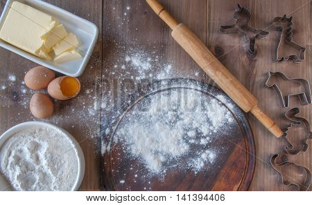 Wooden rustic table with everything you need for baking cookies: rolling pin, eggs, flour, molds to cut biscuits